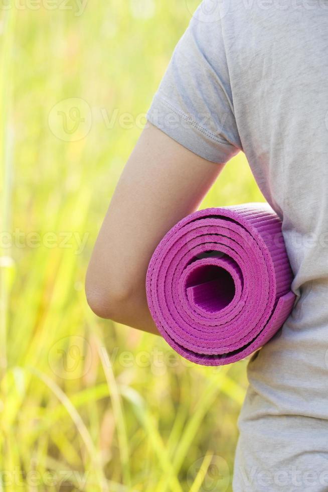junge Frau, die eine Yogamatte hält foto
