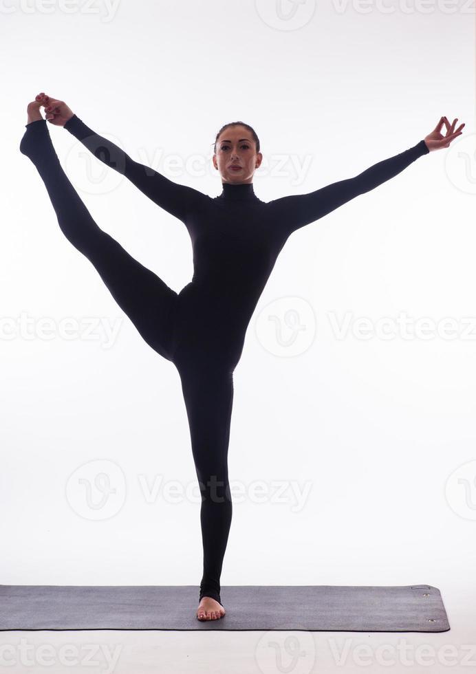 junge schöne Yoga-Frau, die auf einem Studiohintergrund aufwirft foto