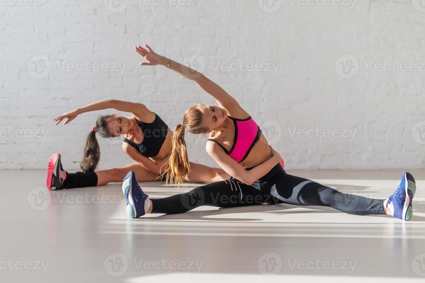 zwei schöne schlanke Fitness-Mädchen, die Yoga-Stretching-Übung kippen foto