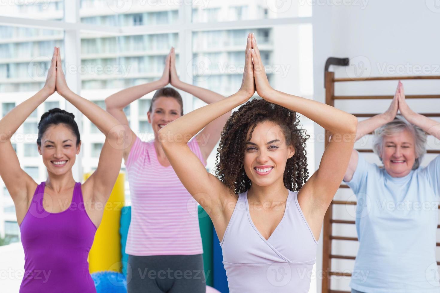 glückliche Freunde, die Baumhaltung im Fitnessstudio üben foto