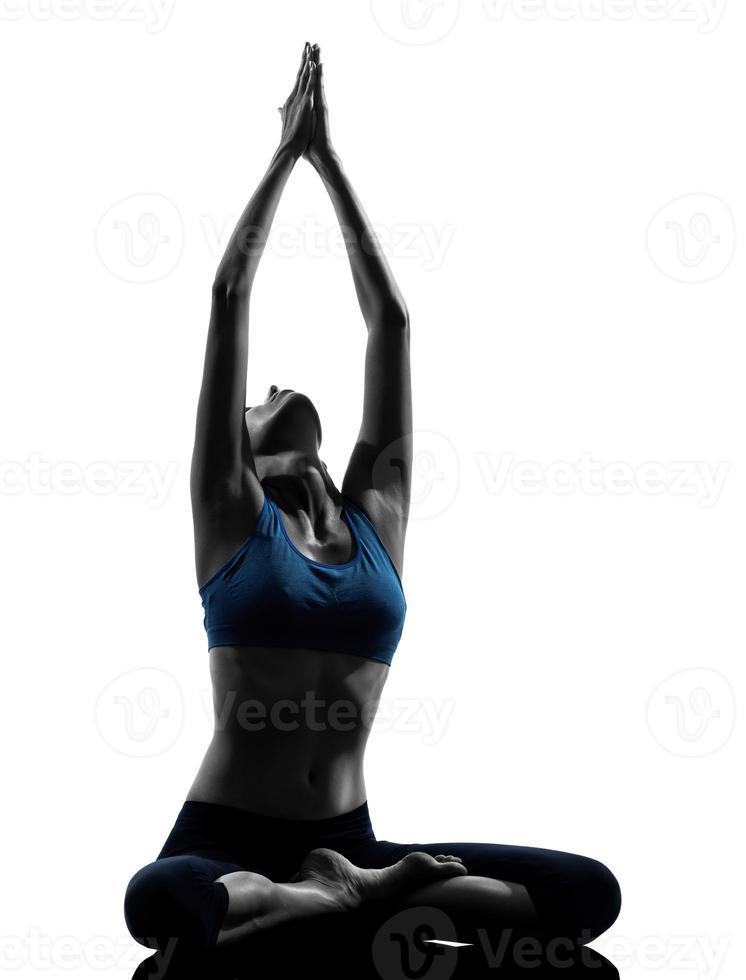 Frau in Yoga-Pose streckt ihre Arme in den Himmel foto