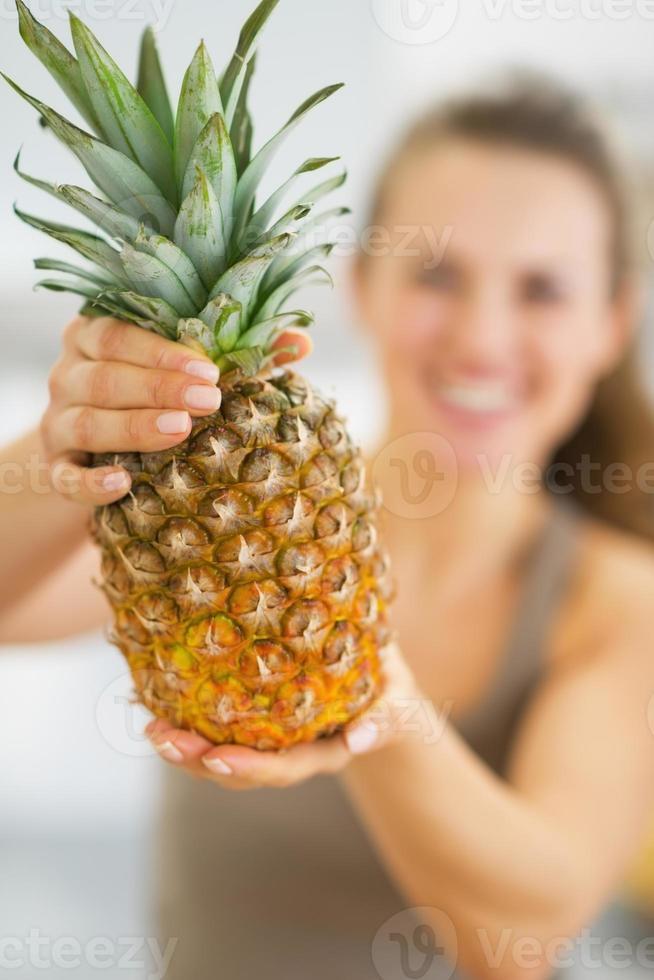 Nahaufnahme auf Ananas in der Hand der glücklichen jungen Frau foto