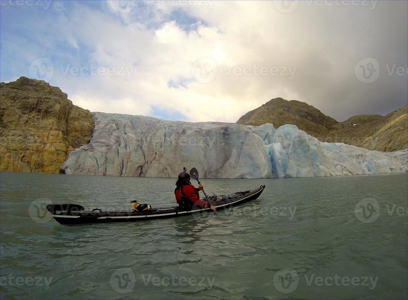 Seekajakfahren in der Nähe eines Gletschers foto