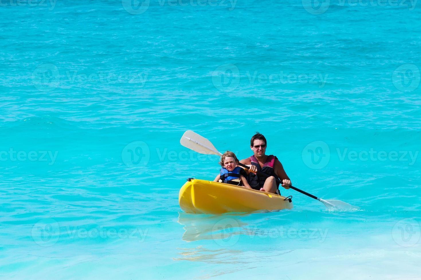 Vater und Sohn auf einem Kajak im tropischen Ozean foto
