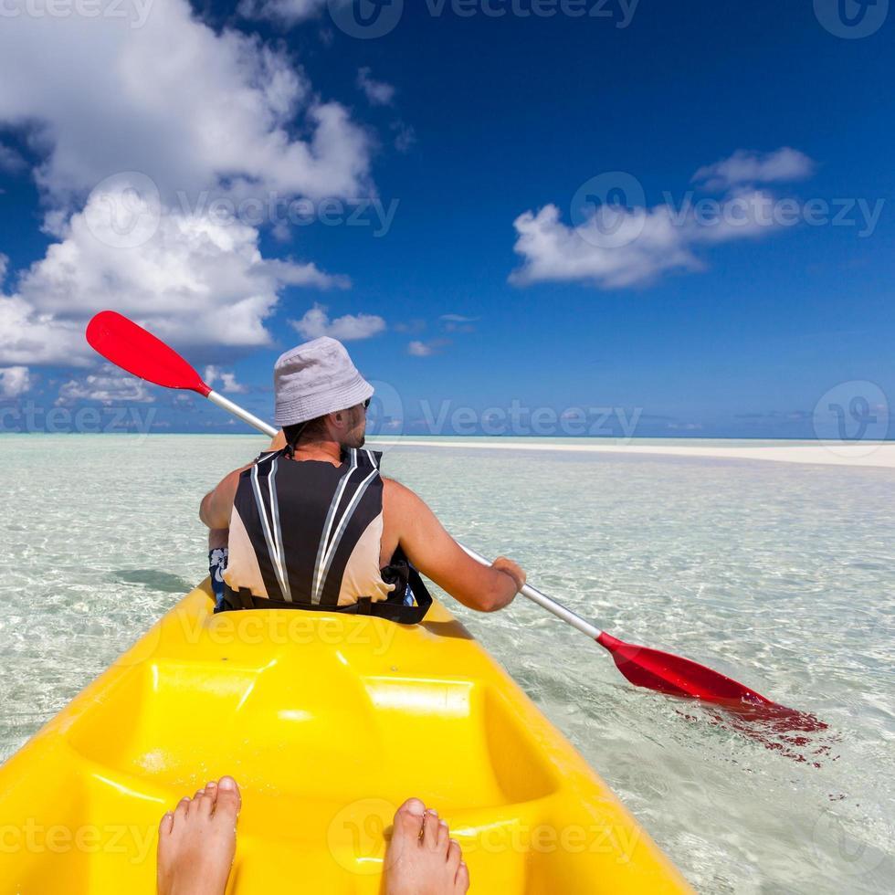 junger kaukasischer Mann, der im Meer auf den Malediven Kajak fährt foto