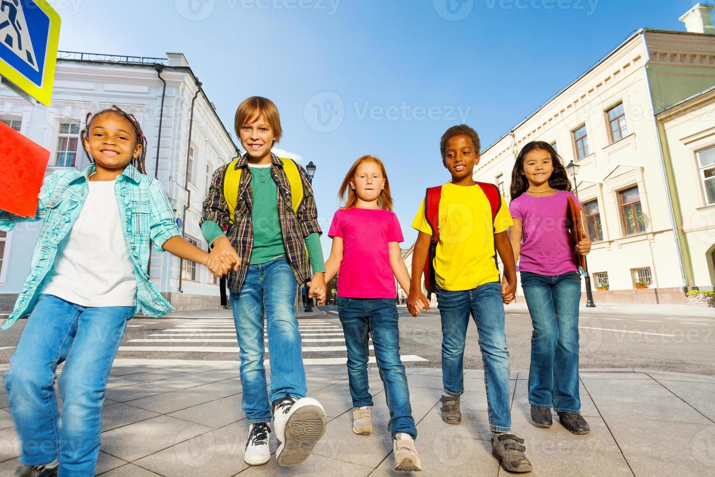 internationale Kinder tragen Taschen und gehen in Reihe foto