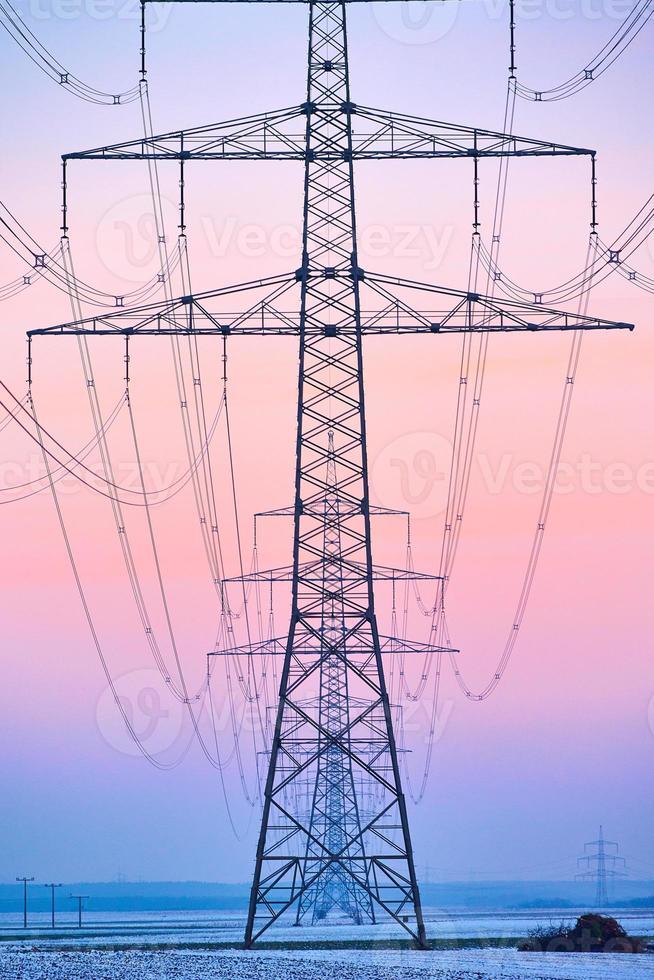 elektrischer Turm in einer Reihe mit großem Himmel foto