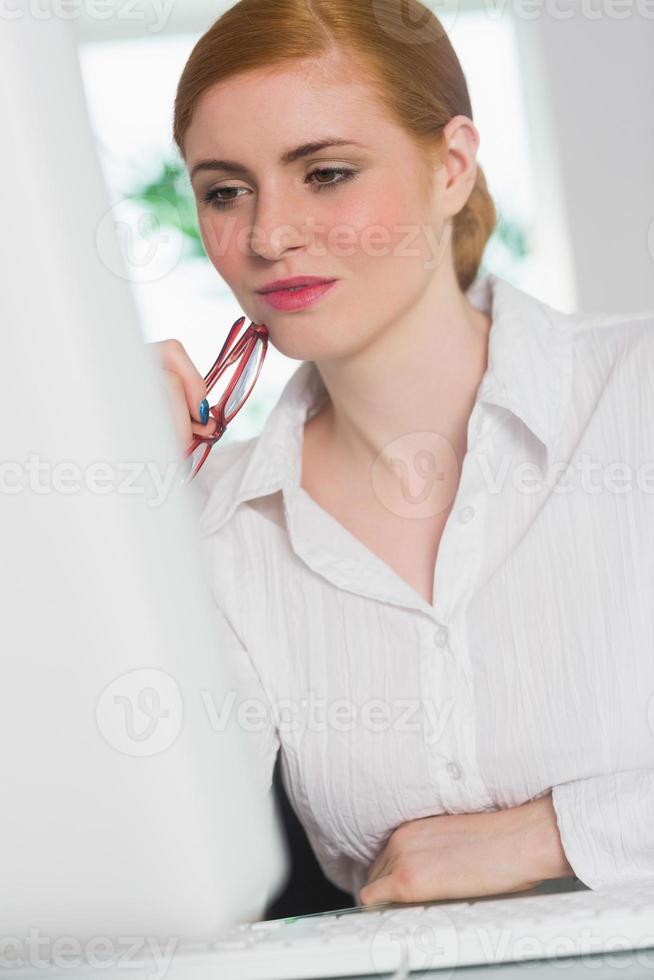fokussierte Geschäftsfrau, die an ihrem Schreibtisch arbeitet und eine Brille hält foto