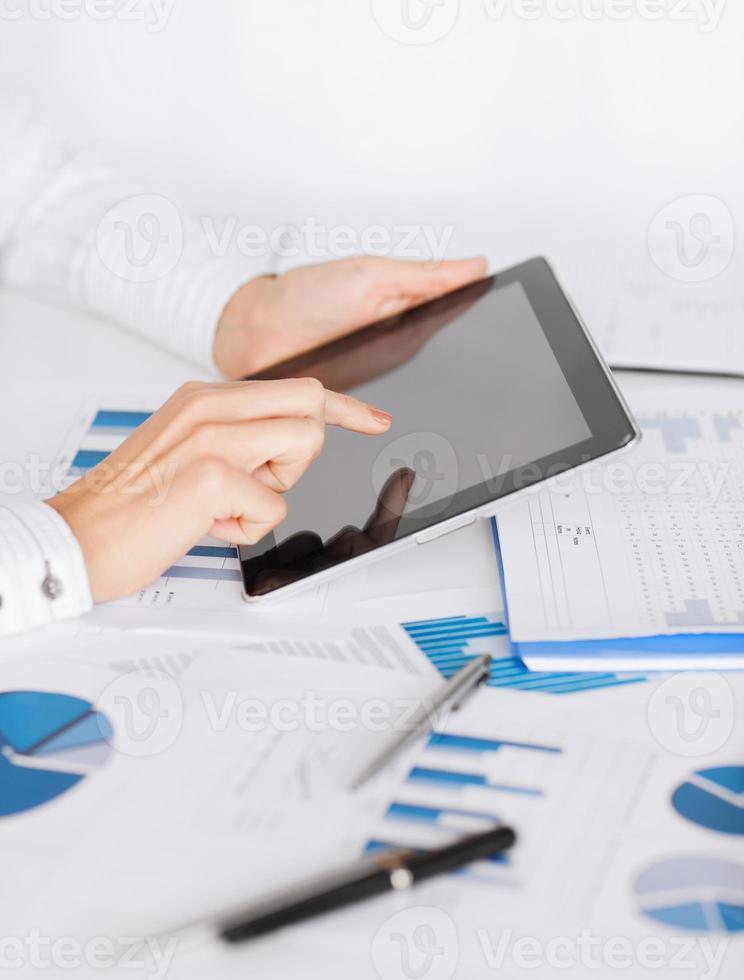 Frau mit Tablet-PC und Diagrammpapieren foto