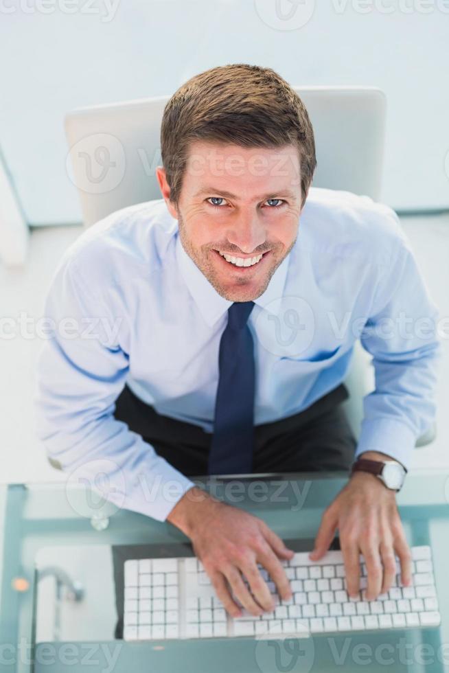 lächelnder Geschäftsmann, der seinen Computer benutzt foto