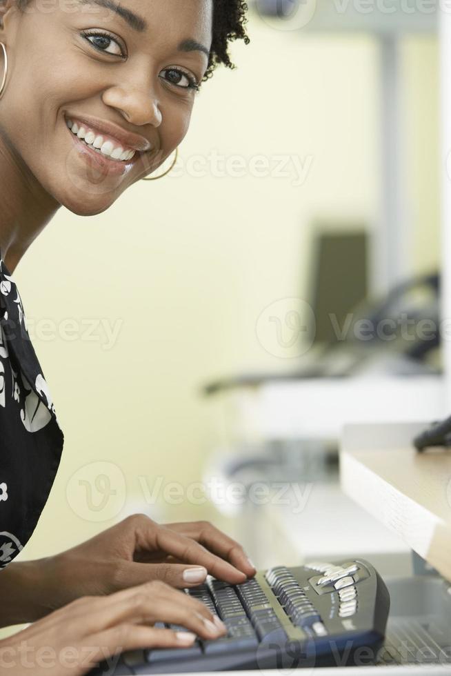 glückliche Geschäftsfrau, die Computer im Büro benutzt foto