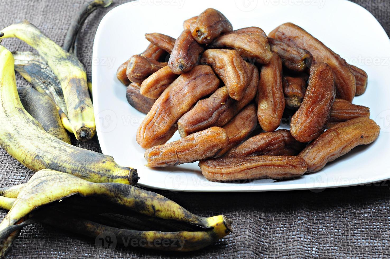 Bananenschale und getrocknete Banane legten einen Teller Weiß. foto