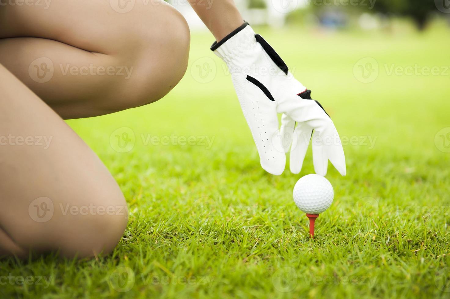 Hand Dame platziert Golfball auf Tee foto