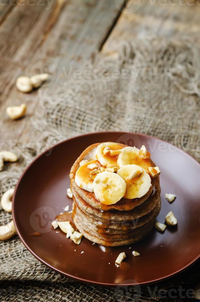 Bananen-Cashew-Pfannkuchen mit Bananen und gesalzener Karamellsauce foto