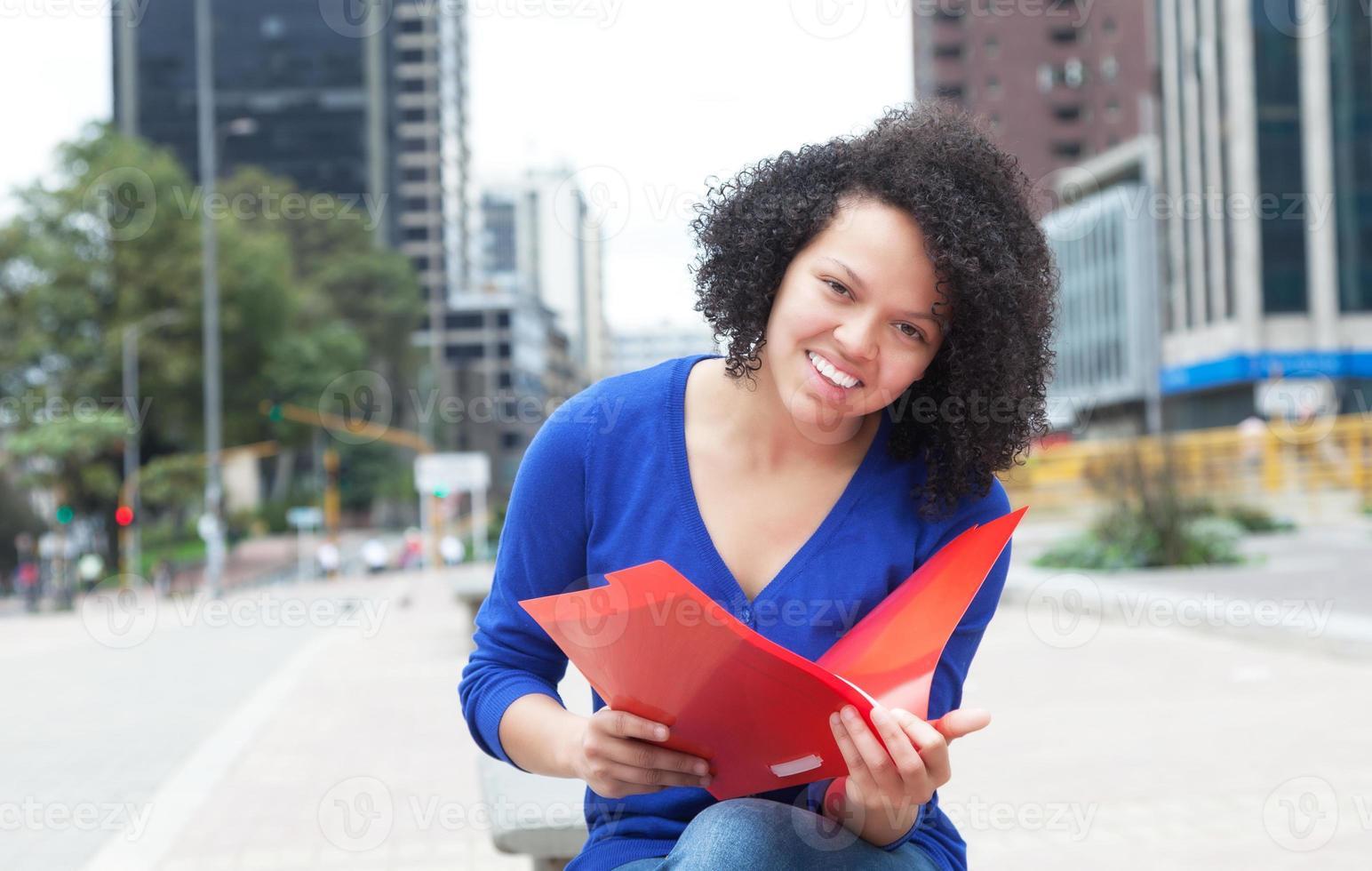 lateinamerikanischer Student mit lockigem Haar in der Stadt foto