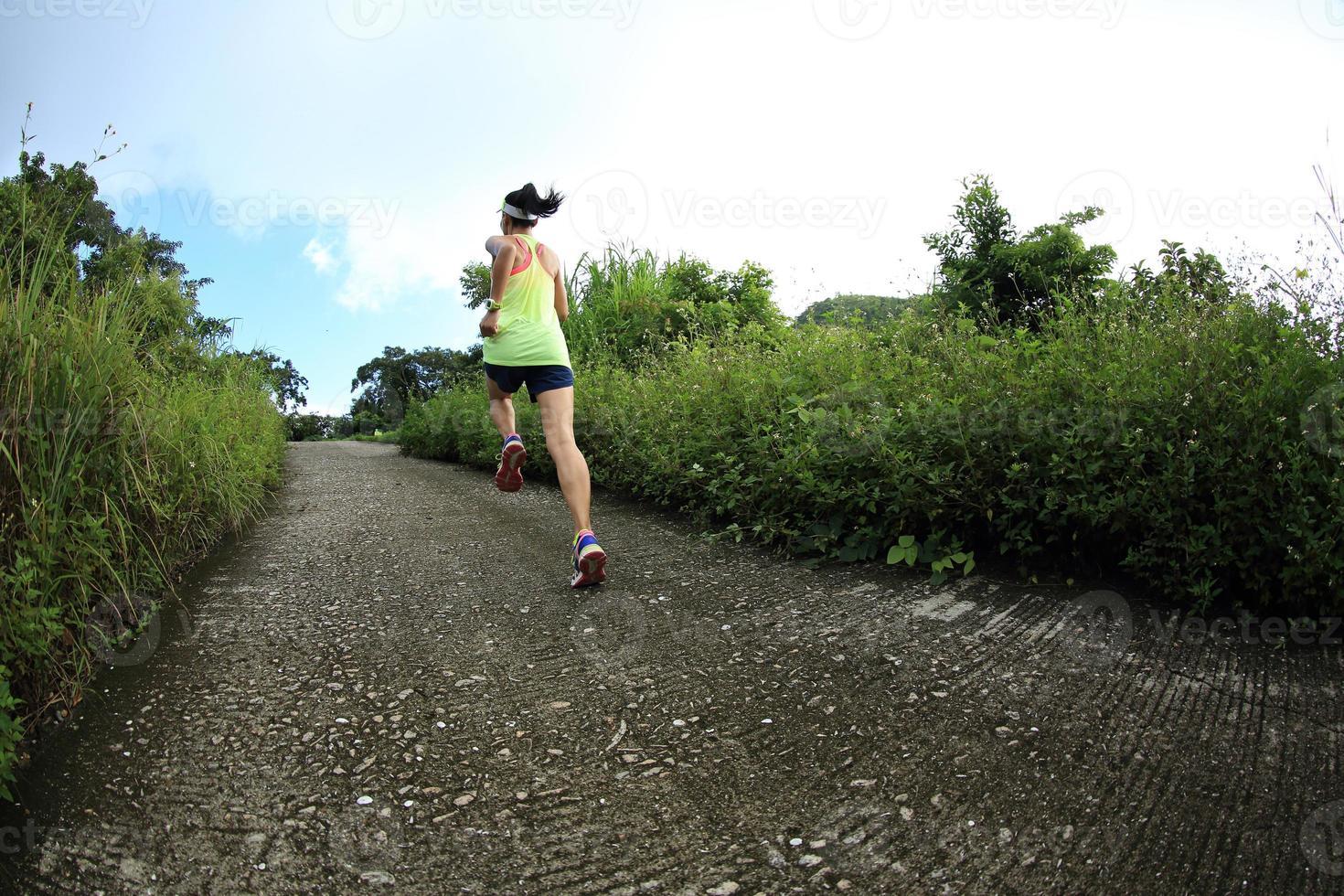 junger Fitnessfrauenläufer, der auf Bergpfad läuft foto