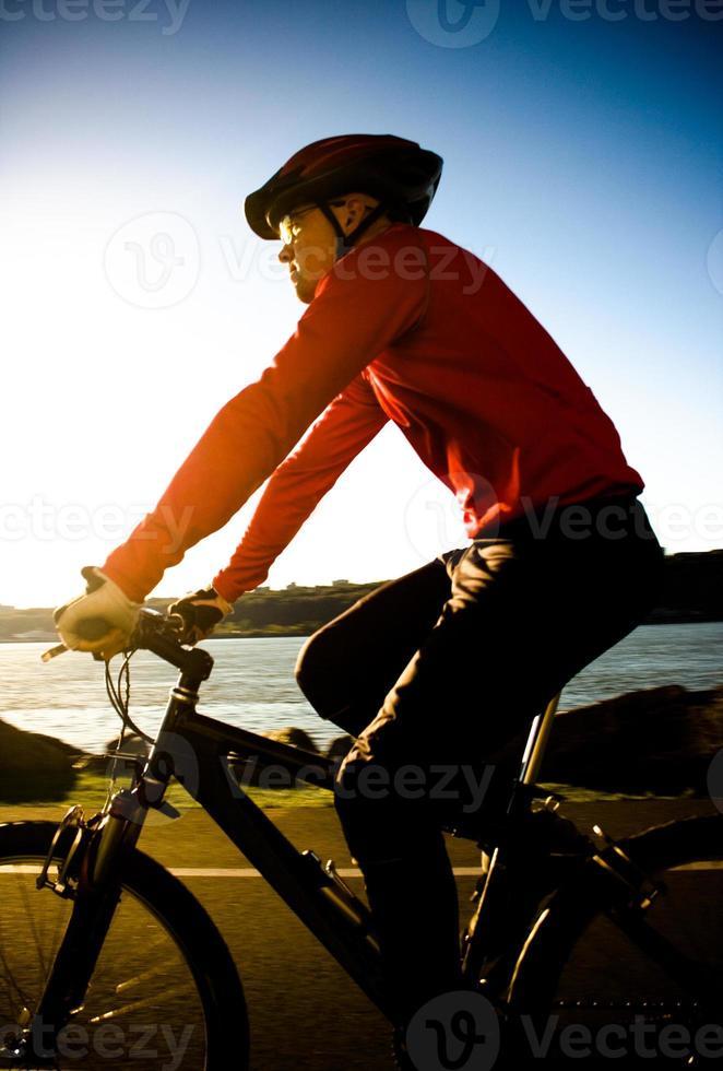 Mann Radfahren während des Sonnenuntergangs foto