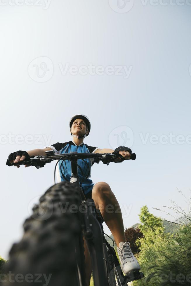 junge Frau, die auf Mountainbike und Radfahren im Park trainiert foto