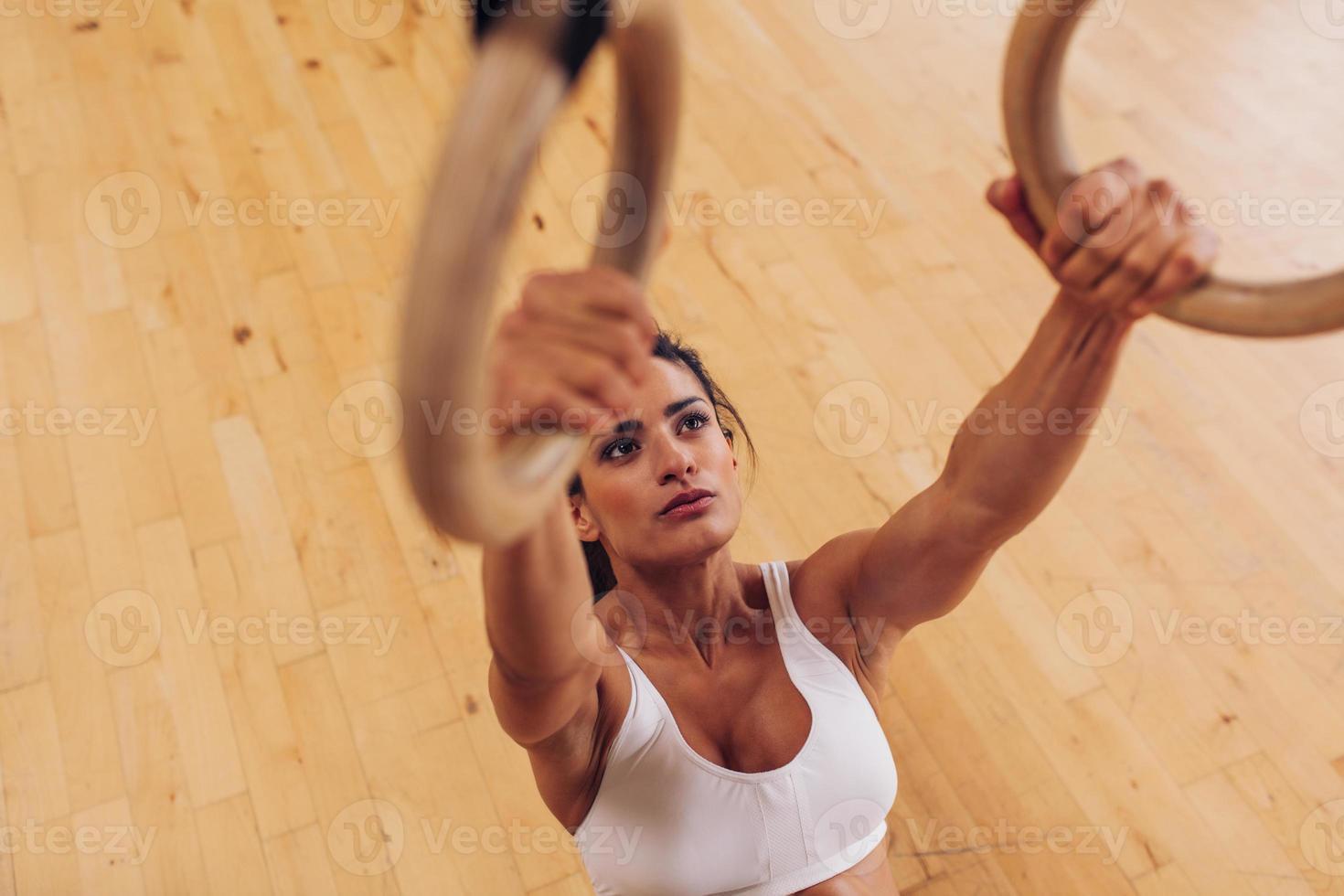 entschlossene junge Frau im Fitnessstudio mit Turnringen foto