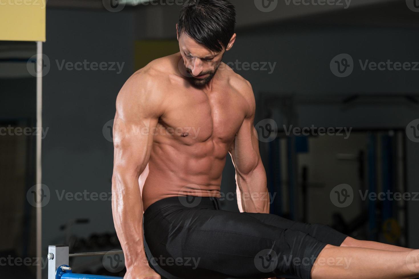Sportler, der schwere Übungen auf Barren macht foto