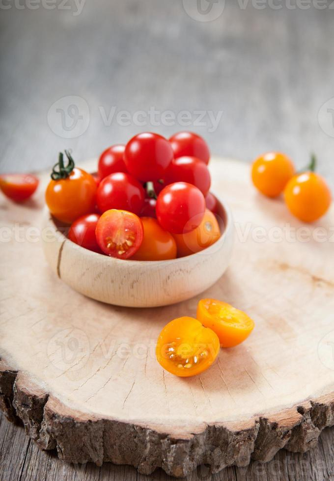 rote und orange Kirschtomaten auf dem dunklen Holztisch foto
