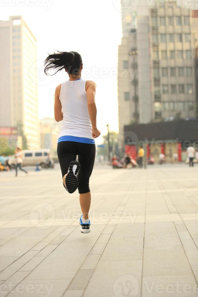 Fitness-Sportfrau des gesunden Lebensstils, die auf Stadtstraße läuft foto