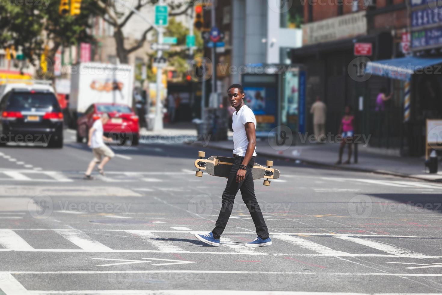 schwarzer Junge, der in der Stadt geht, die Longboard hält foto