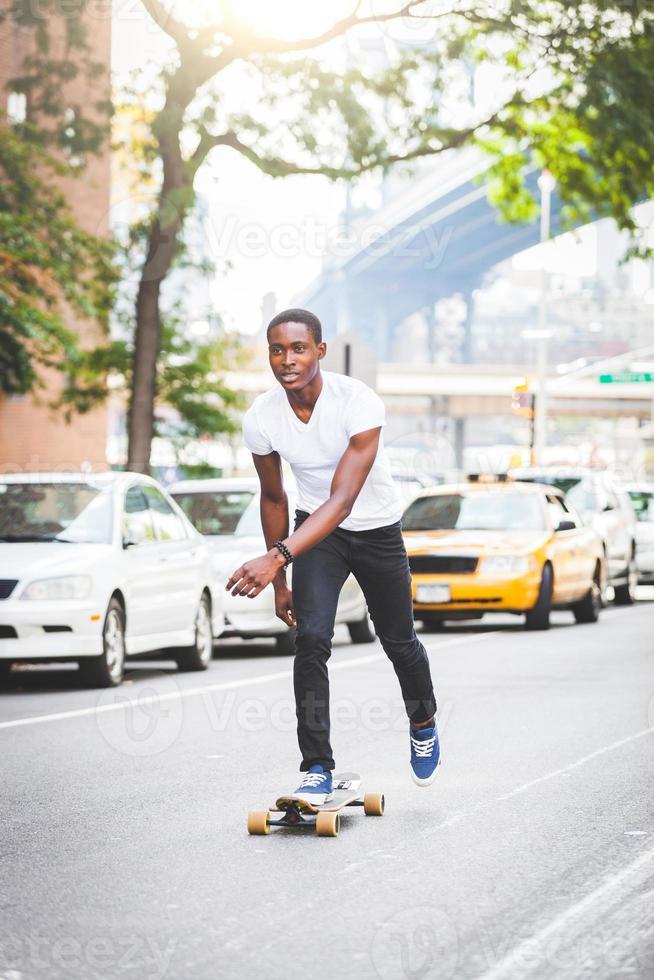 schwarzer Junge, der mit Longboard auf der Straße skatet foto
