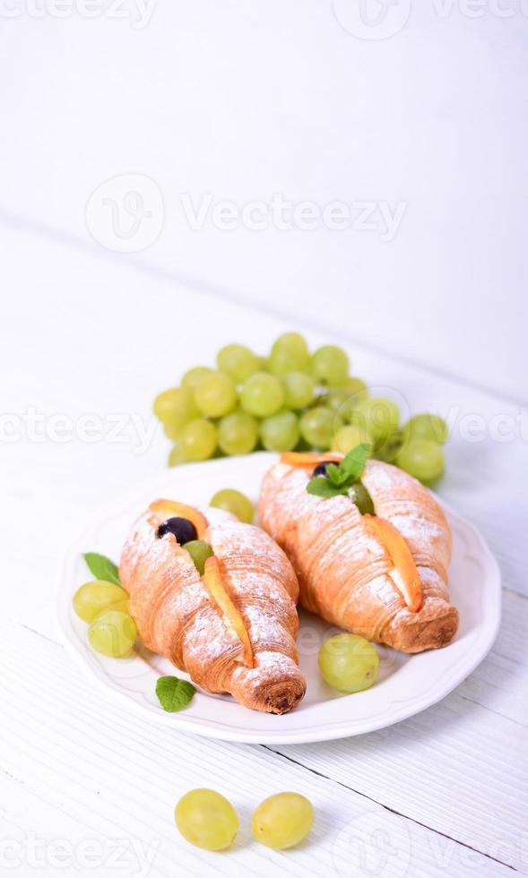 frisches Croissant mit Trauben auf weißem Hintergrund foto