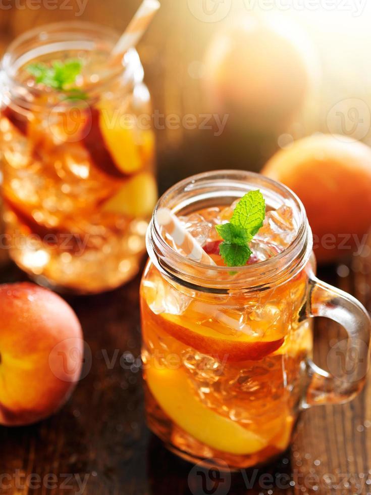 Glas Pfirsich-Tee senkrecht geschossen foto