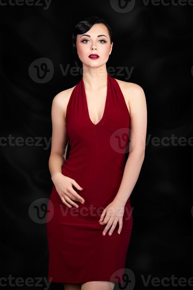 Retro-Art brünette Frau, die über schwarzem Hintergrund aufwirft foto
