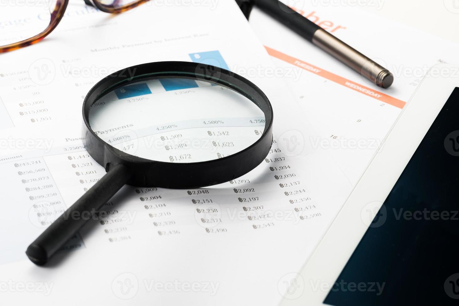 Finanzdokument mit Lupe dokumentieren. Gewinn suchen foto