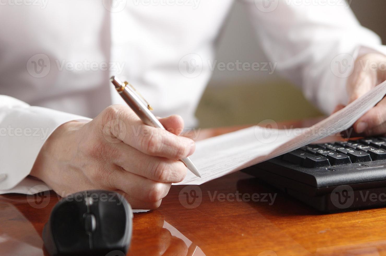 Hände mit Dokument und Stift auf einer Computertastatur foto