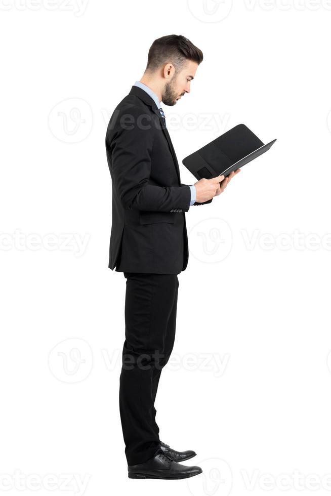 Geschäftsmann im Anzug, der Dokument oder Vertragsseitenansicht liest. foto