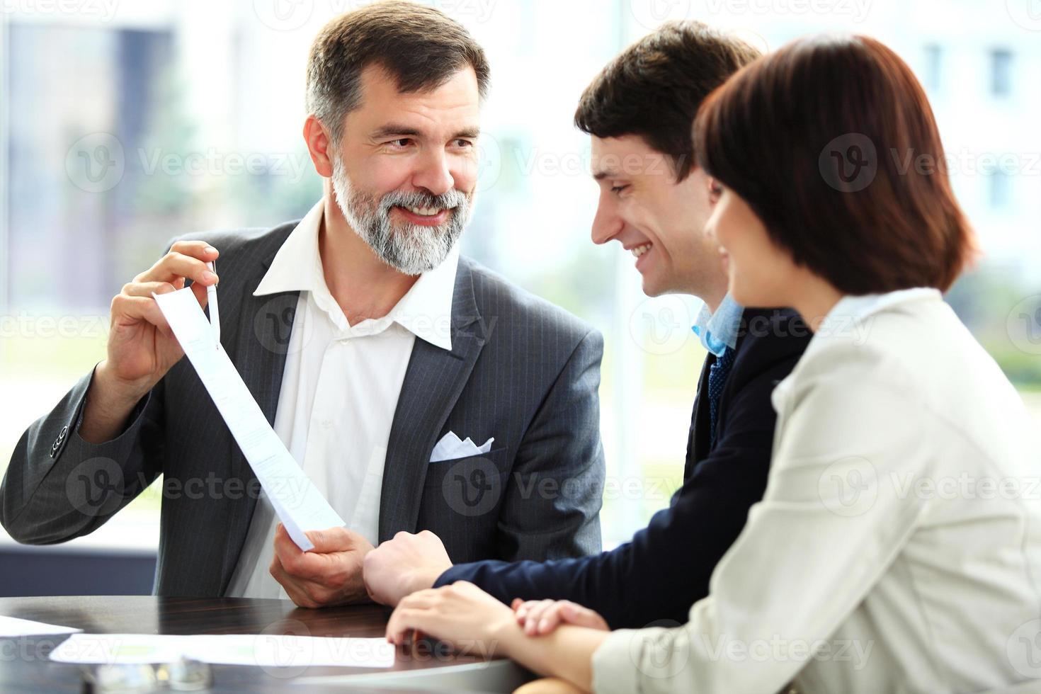 Geschäftspartner diskutieren Dokumente und Ideen beim Treffen foto