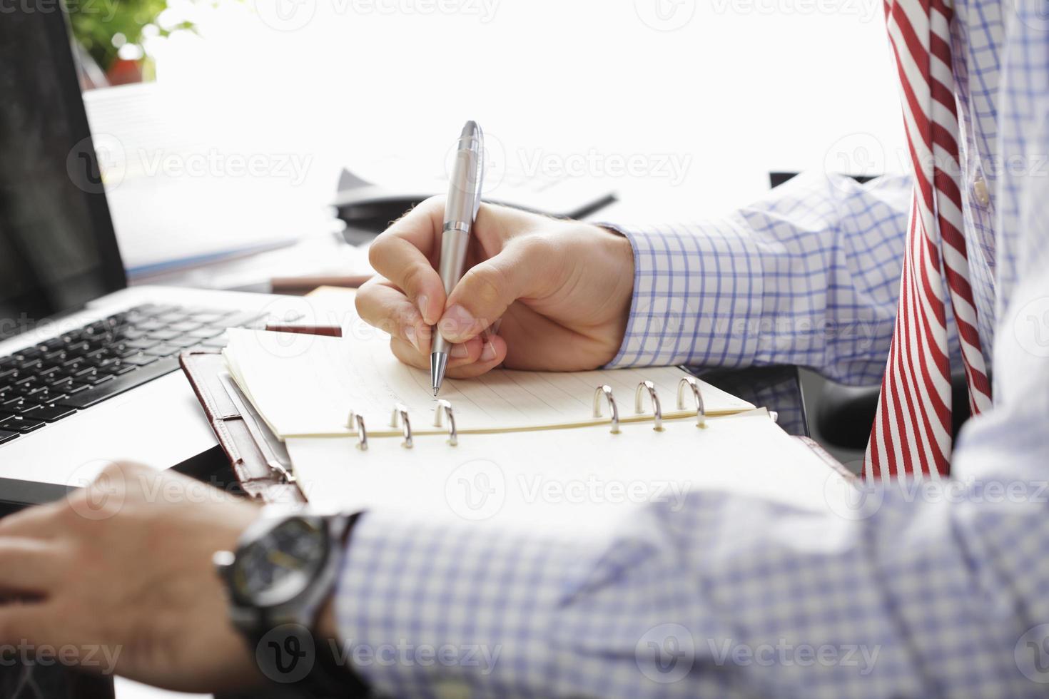 ein Mann, der in seinen persönlichen Kalender schreibt foto