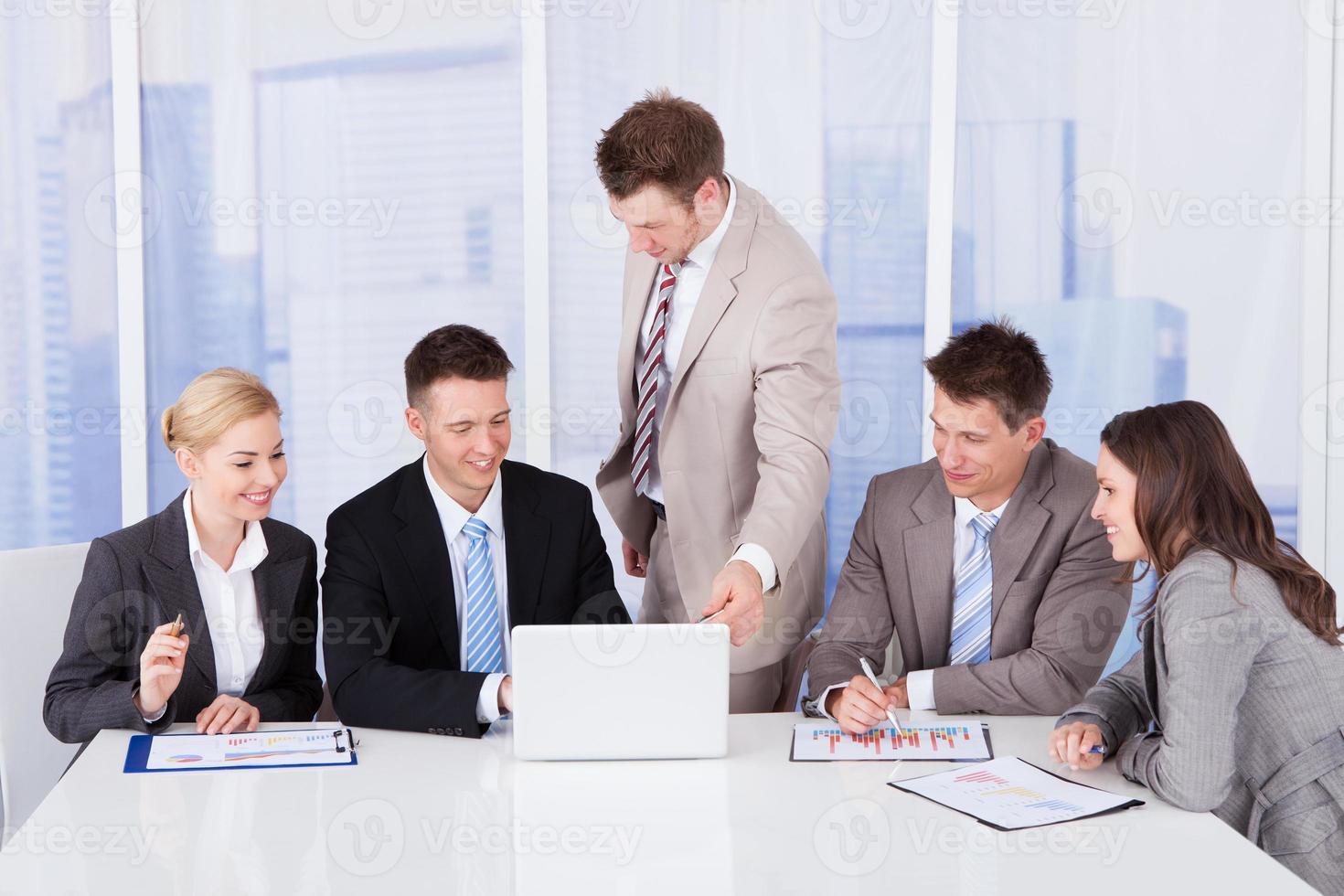 Geschäftsleute diskutieren auf Laptop im Büro foto