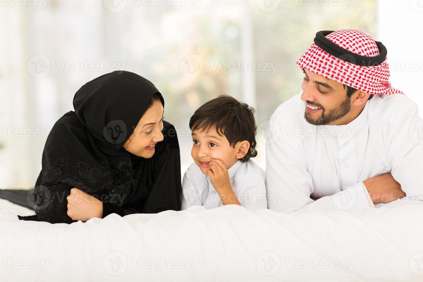 junge muslimische Familie, die auf Bett liegt foto