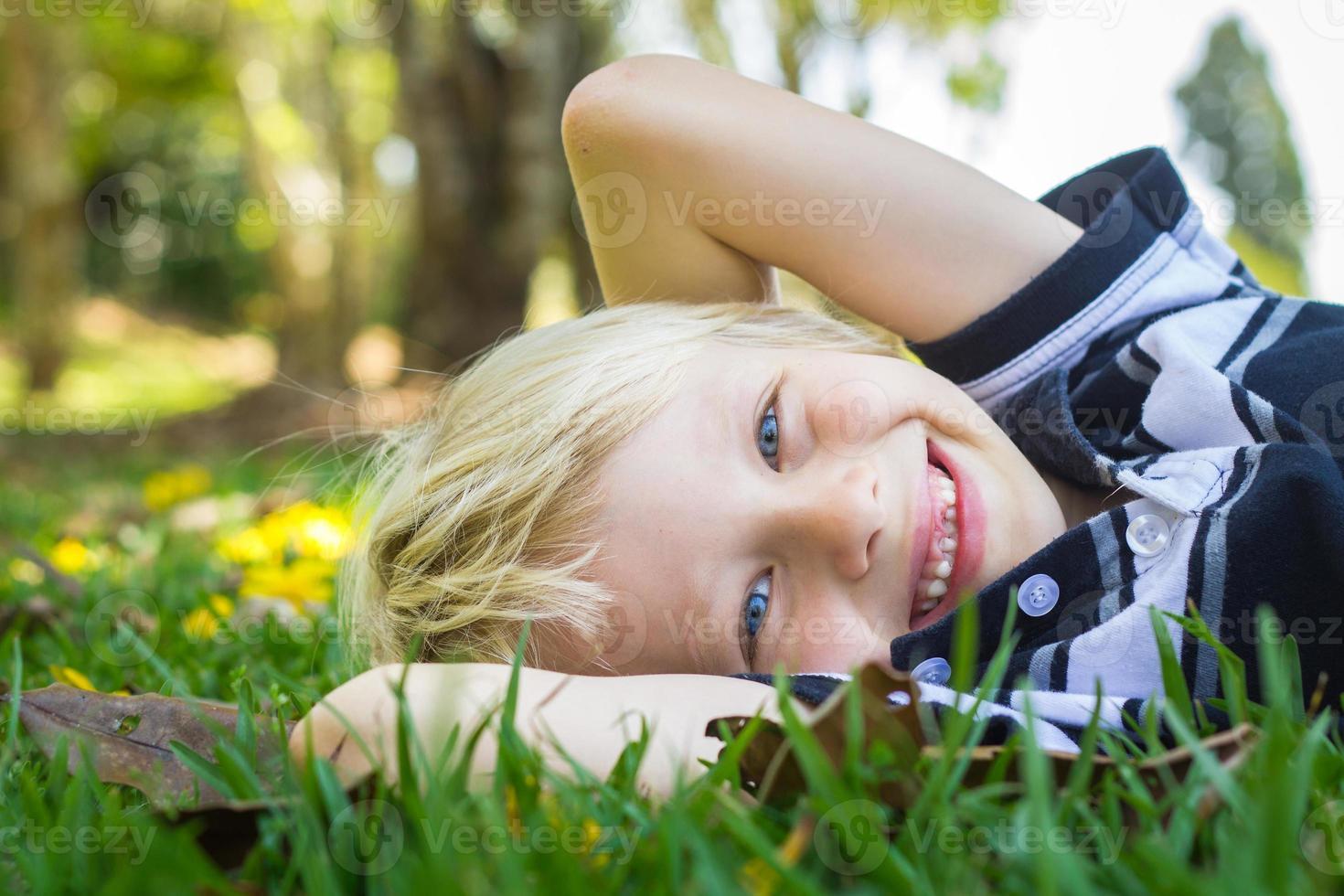 glückliches Kind, das auf dem Gras liegt foto