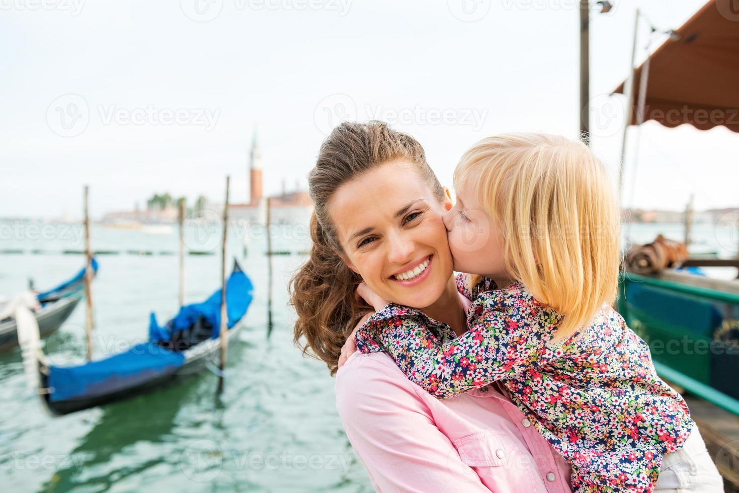 Kind küsst glückliche Mutter in Venedig foto
