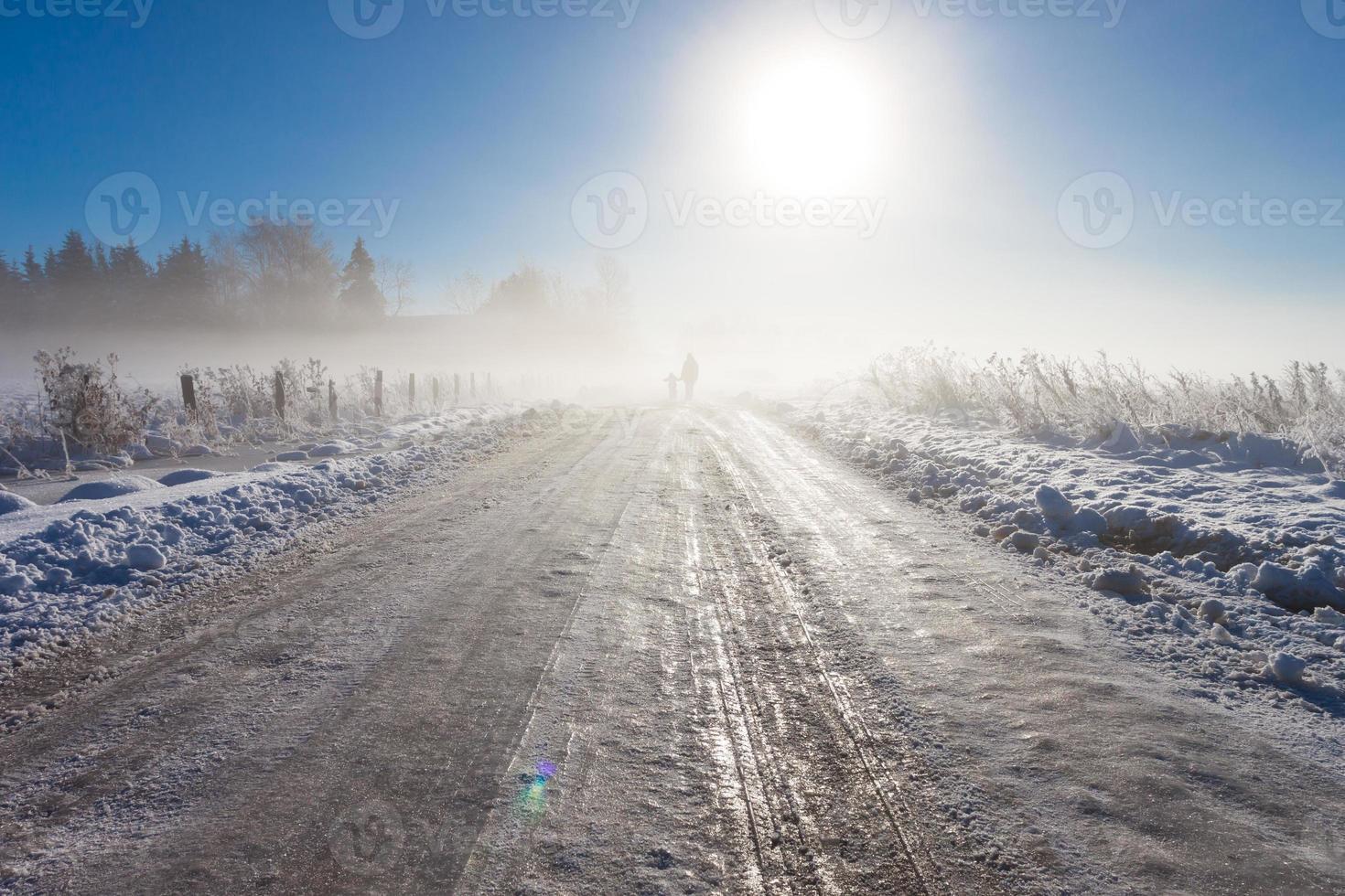 Mutter und Kind auf nebliger Schneestraße foto