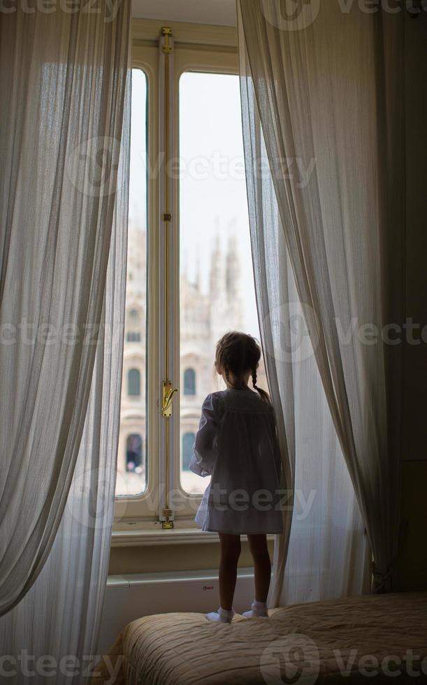 entzückendes kleines Mädchen, das aus dem Fenster auf Dom, Mailand, Italien schaut foto