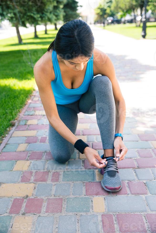 Frau, die ihren Schnürsenkel im Freien bindet foto