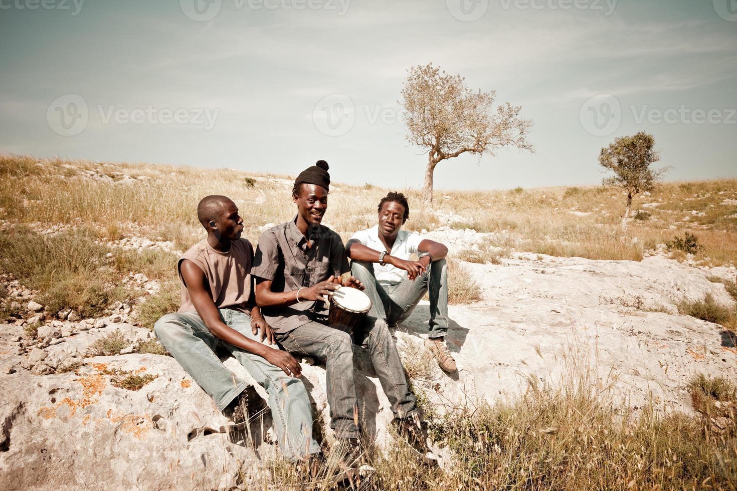 Drei afrikanische Männer spielen Djembe auf der Wiese foto