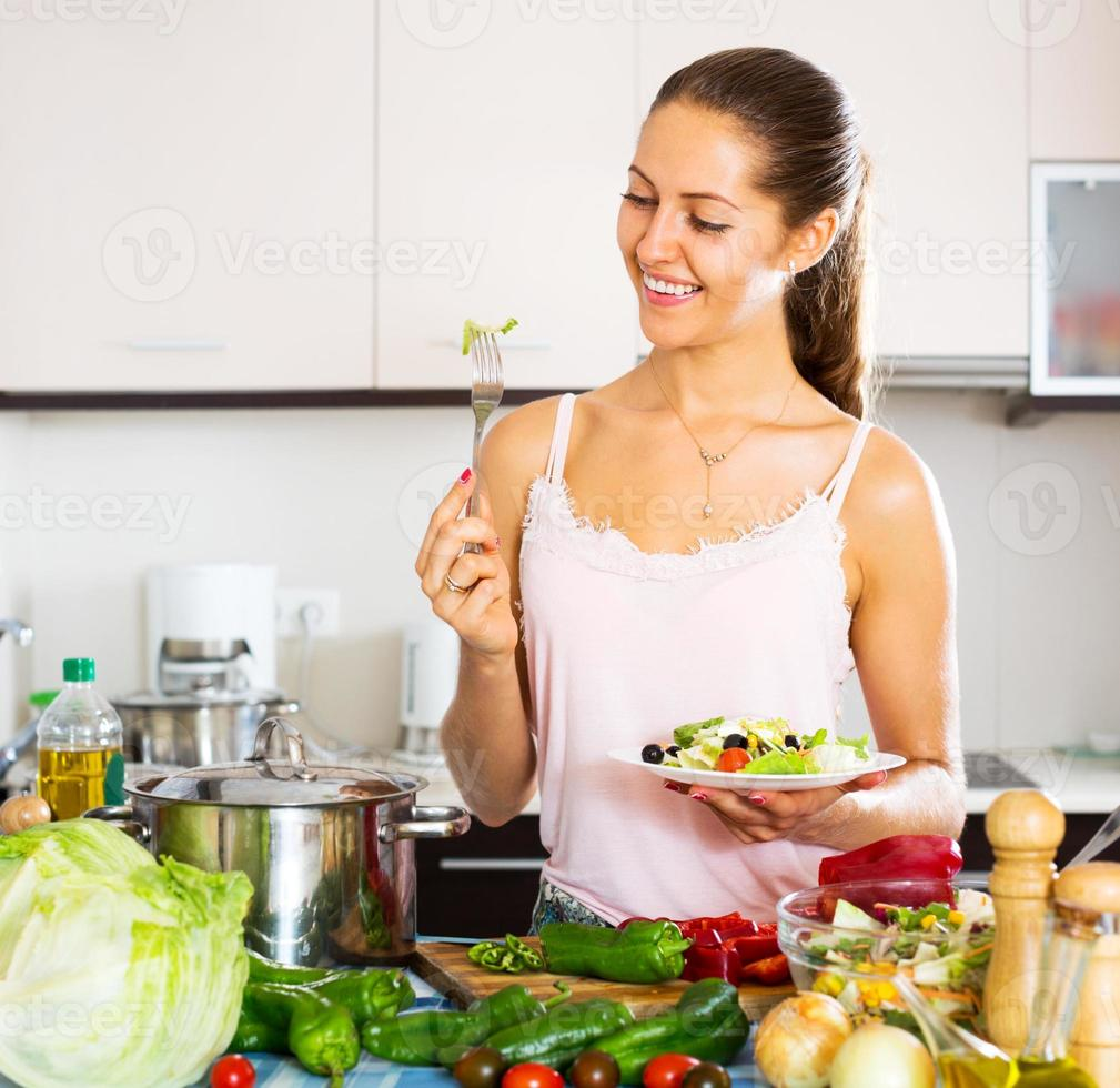 positive Frau, die gesunden Salat isst foto