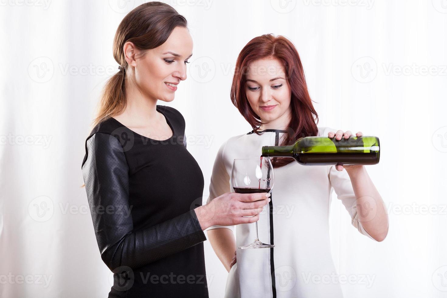 Freundinnen, die Rotwein trinken foto
