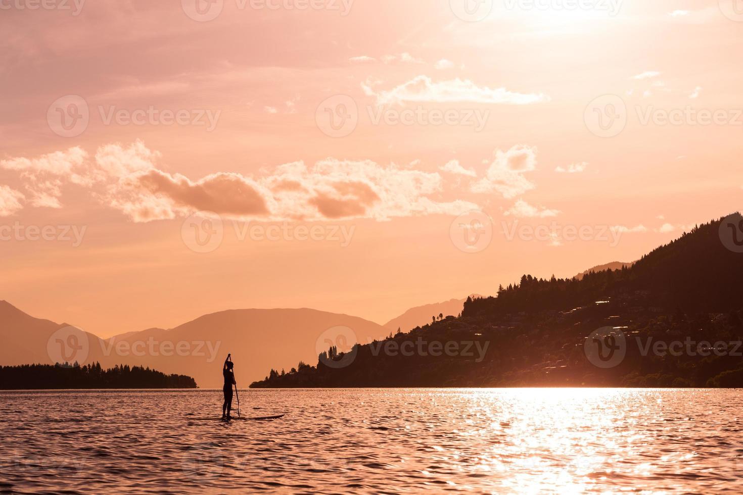 junge Frau paddelt ein Paddleboard foto