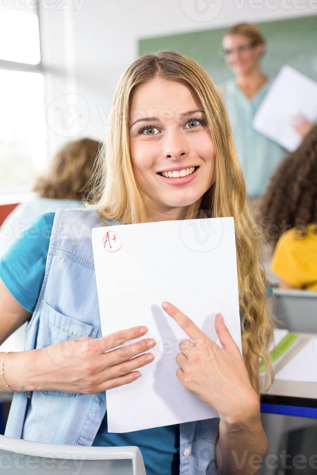schöne Studentin, die auf Papier zeigt foto