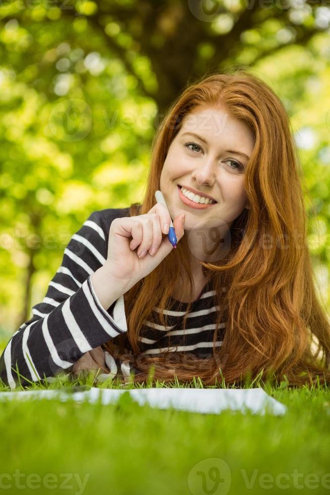 Studentin, die Hausaufgaben im Park macht foto