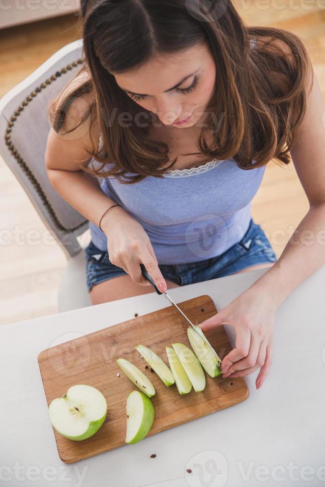 junge Frau schneidet Apfel. Bild von oben. foto